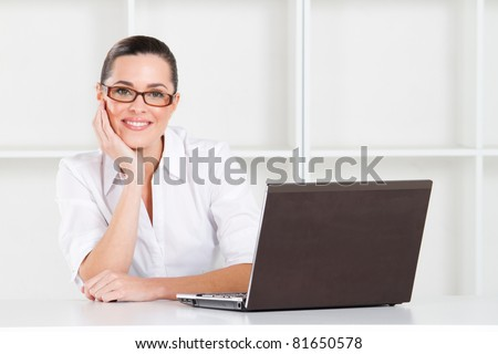 young businesswoman in office with laptop - stock photo