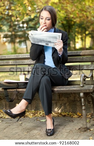 young businesswoman in park on break eating and reading newspaper