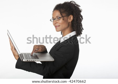 Young businesswoman in profile using laptop. Horizontally framed shot.