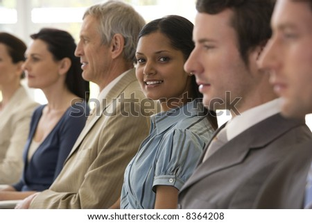 Young businesswoman in seated line with colleagues - stock photo
