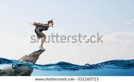 Young businesswoman in suit and diving mask jumping in water - stock photo