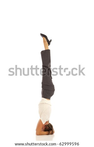 Young businesswoman in suit doing yoga Headstand Pose - stock photo