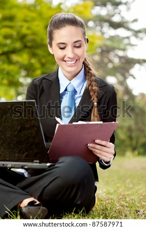 young businesswoman in suit working on grass, making note - stock photo