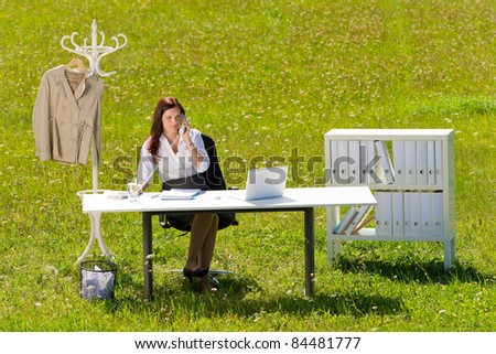 Young businesswoman in sunny meadow nature office calling behind table