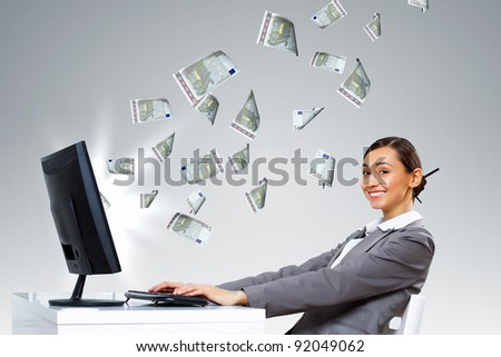 Young businesswoman in the office with money banknotes around her