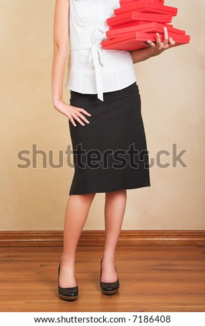 Young businesswoman in white shirt and black pencil skirt holding red gifts boxes - stock photo