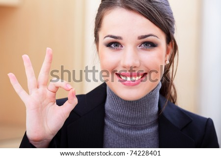 Young businesswoman indicating ok sign.