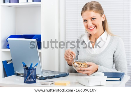 Young businesswoman is eating cereals for breakfast at work,Healthy breakfast - stock photo