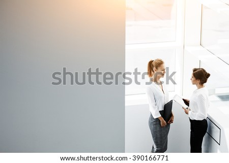 Young businesswoman is holding digital tablet and talking something to her secretary,while they are standing in office interior near copy space for your advertising text message or promotional content - stock photo