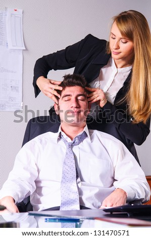 young businesswoman is making head massage to her teammate - stock photo