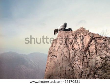 Young businesswoman kneeling on a mountain peak and looking downwards - stock photo
