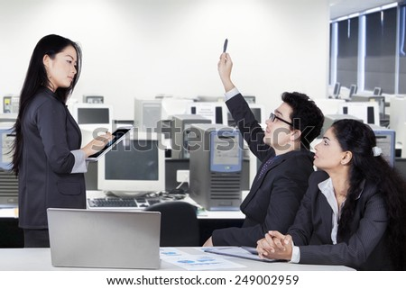 Young businesswoman lead a business meeting in the office room with two partners - stock photo