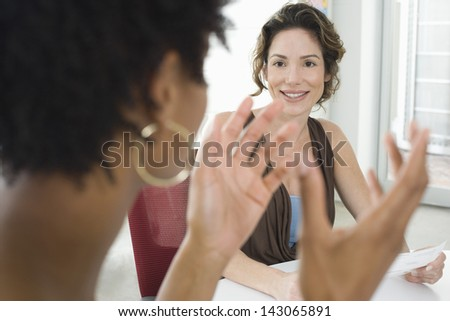 Young businesswoman listening to female colleague during meeting in office - stock photo