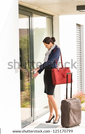 Young businesswoman locking door traveling luggage leaving home bag - stock photo
