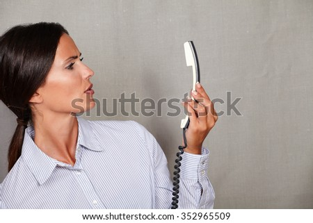 Young businesswoman looking angry at the phone without speaking on grey texture background - stock photo
