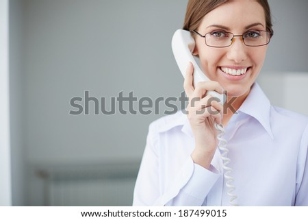 Young businesswoman looking at camera while speaking on the phone - stock photo