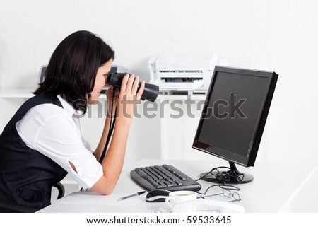 young businesswoman looking at computer monitor with binoculars - stock photo