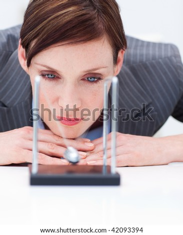 Young businesswoman looking at kinetic balls in the office - stock photo