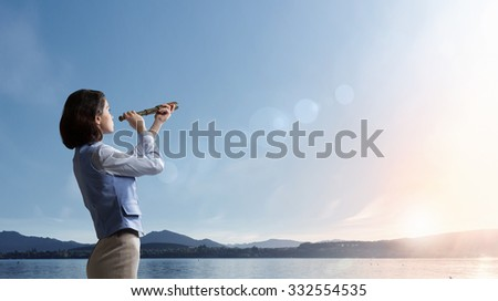 Young businesswoman looking in spyglass on sunrise at horizon - stock photo