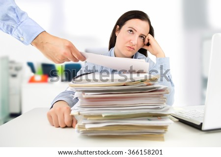 young businesswoman looking overwhelmed while surrounded by paperwork - stock photo