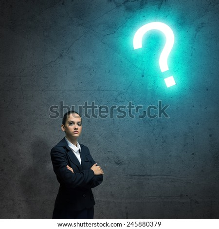 Young businesswoman looking thoughtfully at question mark - stock photo