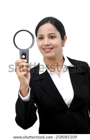 Young businesswoman looking through a magnifying glass - stock photo