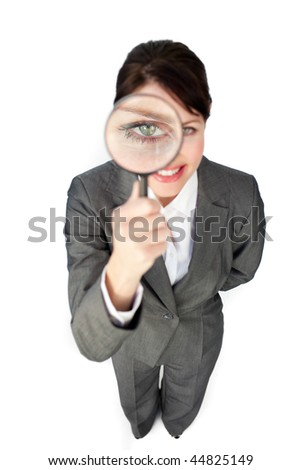 Young businesswoman looking through magnifying glass against a white background