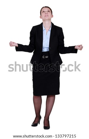 young businesswoman looking upwards tight-fisted - stock photo