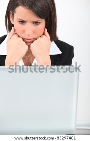 young businesswoman looking worried in front of laptop - stock photo