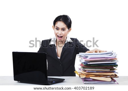 Young businesswoman looks shocked with a pile of paperwork and laptop computer on the table - stock photo