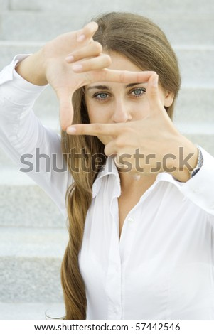 Young businesswoman looks through a frame made of hand - stock photo