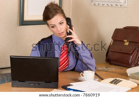 Young businesswoman making call with laptop at office