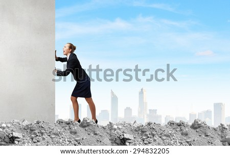 Young businesswoman making effort to move wall - stock photo