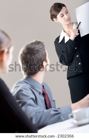 Young businesswoman making presentation and two blurred business person at office