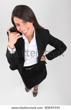 Young businesswoman mobile telephone gesture with hand - stock photo