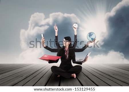 Young businesswoman multitasking under outdoor - stock photo
