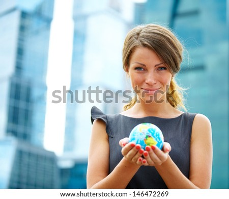 young businesswoman near office buildings with globe of earth - stock photo