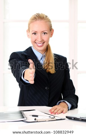 Young businesswoman offering handshake in the office