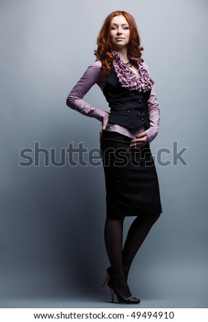 Young businesswoman on gray wall background. - stock photo