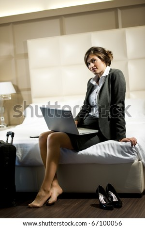 Young businesswoman on laptop in her hotel room - stock photo