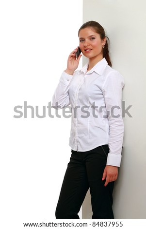 Young businesswoman on phone against wall