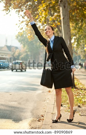 young businesswoman on street trying to hail taxi cab - stock photo