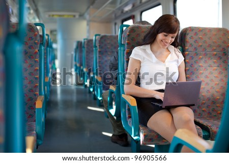 Young businesswoman on the move. Using laptop on the train / bus