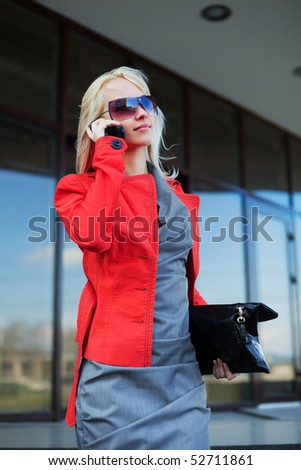 Young businesswoman on the phone against office building. - stock photo