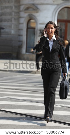 Young businesswoman on the phone crossing the street in a city.