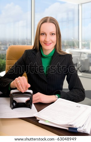 Young businesswoman (or notary public) seating at the desk in office and stamping document - stock photo