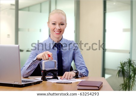 Young businesswoman (or notary public) sitting at the desk in office and stamping document looking at camera