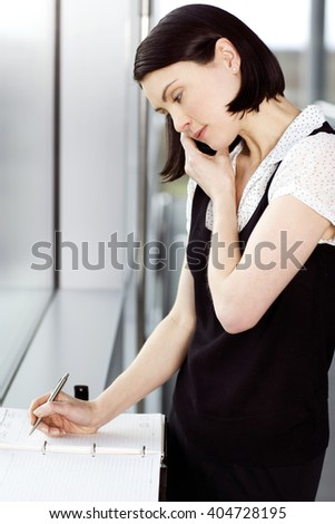 Young businesswoman or secretary making an appointment in a diary - stock photo