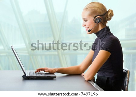 Young businesswoman or secretary with headset and laptop at office - stock photo