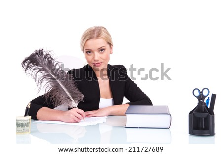 Young businesswoman or teacher working at her desk. beautiful young woman writing at table using feather - stock photo
